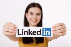 基辅,乌克兰- 2016年8月22日:妇女在白色背景的纸递拿着Linkedin商标标志打印 Linkedin 库存照片