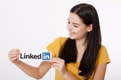 基辅,乌克兰- 2016年8月22日:妇女在白色背景的纸递拿着Linkedin商标标志打印 Linkedin 免版税库存照片