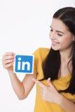 基辅,乌克兰- 2016年8月22日:妇女在白色背景的纸递拿着Linkedin象标志打印 Linkedin 免版税库存照片
