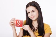 基辅,乌克兰- 2016年8月22日:妇女递拿着谷歌加上在灰色背景的纸打印的象 谷歌是美国 图库摄影