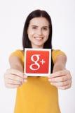 基辅,乌克兰- 2016年8月22日:妇女递拿着谷歌加上在灰色背景的纸打印的象 谷歌是美国 库存图片