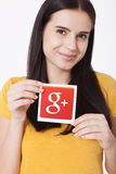 基辅,乌克兰- 2016年8月22日:妇女递拿着谷歌加上在灰色背景的纸打印的象 谷歌是美国 免版税库存图片
