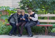 基辅,乌克兰- 2015年9月10日:学生坐长凳在智能手机帮助下使用了 库存图片