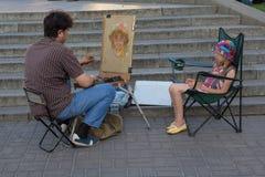 基辅,乌克兰- 2016年6月19日:街道艺术家绘女孩的画象 免版税库存照片