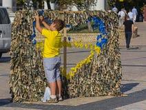 基辅,乌克兰- 2015年9月20日::男孩编织与国家标志的稀松窗帘用布 免版税库存照片