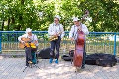 基辅,乌克兰- 2017年6月04日 街道音乐家:吉他弹奏者、萨克斯管吹奏者和低音演奏员,在街道上的戏剧 水平的框架 库存图片