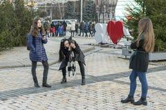 基辅,乌克兰 12月17日2017 A女孩为在街道上的一个女朋友照相 旅行概念-愉快的旅游采取的p 库存图片