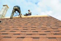 基辅-乌克兰, 10月- 18日2016年:屋顶承包商安装与沥青木瓦的新房屋顶 免版税库存图片