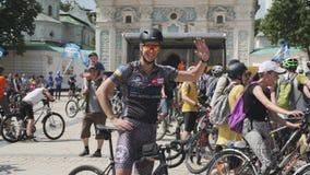 基辅/乌克兰6月,微笑和摇手的1 2019可爱的骑自行车者 逗人喜爱的年轻男孩画象循环的服装和sunglasse的 股票录像