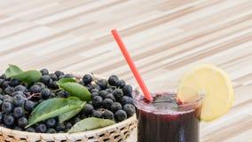 堂梨属灌木在玻璃和莓果的Aronia melanocarpa新鲜的汁液在罐 免版税库存图片