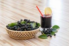 堂梨属灌木或Aronia melanocarpa新鲜的汁液与冰和柠檬在玻璃和莓果在baske 图库摄影