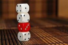 堆三白色塑料切成小方块和在棕色木板背景的一个红色模子 与黑小点的六个边立方体 第1, 2, 免版税库存图片