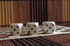 堆三白色塑料在棕色木板背景切成小方块 与黑小点的六个边立方体 第5 免版税库存图片