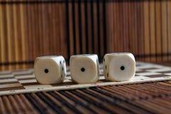 堆三白色塑料在棕色木板背景切成小方块 与黑小点的六个边立方体 第1 免版税图库摄影