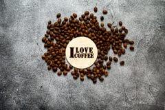 堆与'我爱咖啡'木钢板蜡纸的烤咖啡豆 免版税库存图片