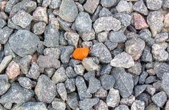 堆与一块明亮的橙色石头的岩石在中间背景中 免版税图库摄影