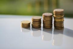 堆与反射的硬币在白色桌上 免版税库存图片