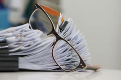 堆与夹子的文件夹在报告的书桌和玻璃上在办公室在早晨 免版税库存图片