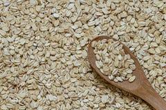 堆与木匙子的捣毁的燕麦种子 免版税库存图片