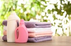堆与洗涤剂的清洁毛巾在反对被弄脏的背景的桌上 库存照片