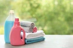 堆与洗涤剂的清洁毛巾在反对被弄脏的背景的桌上 库存图片