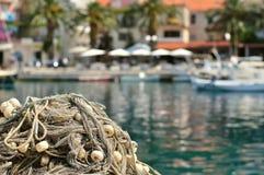 堆与浮游物的捕鱼网在与被弄脏的小船的一个码头在背景 免版税库存图片