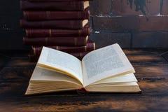 堆与深红坚硬盖子的书和在一张木桌上的开放书以棕色砖墙为背景 免版税库存照片