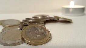 堆与烛光焰的欧洲硬币在背景 免版税库存照片