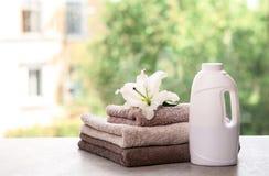 堆与百合和洗涤剂的清洁毛巾在反对被弄脏的背景的桌上 免版税库存图片