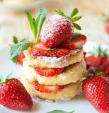 堆与草莓切片的自创凝乳薄煎饼 免版税库存照片