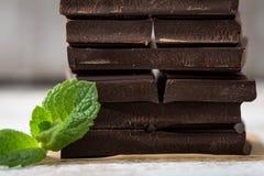 堆与薄荷的叶子的巧克力切片 在wo的黑暗的巧克力 免版税图库摄影