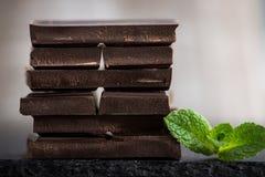 堆与薄荷的叶子的巧克力切片 在wo的黑暗的巧克力 图库摄影