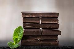堆与薄荷的叶子的巧克力切片 在wo的黑暗的巧克力 免版税库存图片