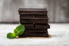 堆与薄荷的叶子的巧克力切片 在wo的黑暗的巧克力 库存照片