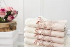 堆与鞋带和珍珠的干净的软的白色和桃红色毛巾 在背景的花 库存图片