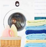 堆与洗涤剂和洗衣机的毛巾 免版税库存图片