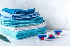 堆与洗涤剂的毛巾在洗衣店背景大模型 免版税库存照片