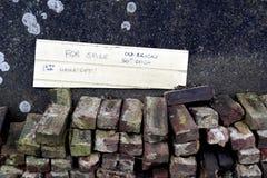 堆与a的老使用的被回收的房子砖待售标志 库存图片