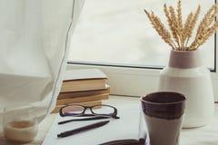 堆书、仁咖啡,花束,玻璃、笔记本和笔在窗口 库存照片