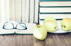 堆书、开放书、玻璃和绿色苹果,学会概念的教育的背景 库存照片