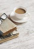 堆书、开放干净的笔记薄、玻璃和一个杯子在一张白色木桌上的可可粉 免版税图库摄影