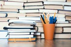 堆书、笔记本和铅笔在塑料持有人在木桌上与拷贝空间文本的 免版税库存照片