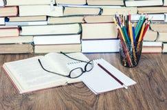 堆书、精装书书在木桌上,开放书、笔记本和玻璃,拷贝空间文本的 库存图片