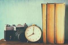 堆书、老时钟和葡萄酒照相机在木桌 图象处理与减速火箭的退色的样式 库存图片