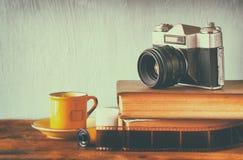 堆书、老时钟和葡萄酒照相机在木桌 图象处理与减速火箭的退色的样式 免版税图库摄影