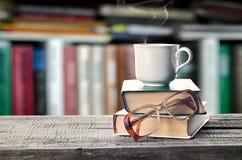 堆书、玻璃和杯子在桌上 免版税库存图片