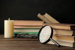 堆书和一个放大器在一张棕色木桌上和在黑背景 登记老 教育 学校 库存照片