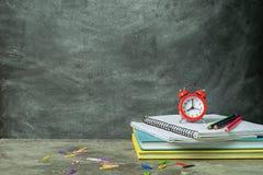 堆书和一个红色闹钟教育笔记本在粉笔板的背景 概念教育 免版税图库摄影