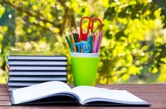 堆书和一块玻璃与色的铅笔 一套在绿色玻璃的文具项目 在一张木桌上的一本开放书 免版税图库摄影