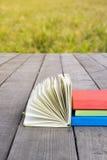 堆书和开放书与被扇动的页在木地板a上 库存图片